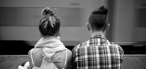 Illustration zu Mobilität und Gerechtigkeit: Eine junge Frau und ein junger Mann sitzen nebeneinander in einer U-Bahn-Station, von hinten zu sehen.