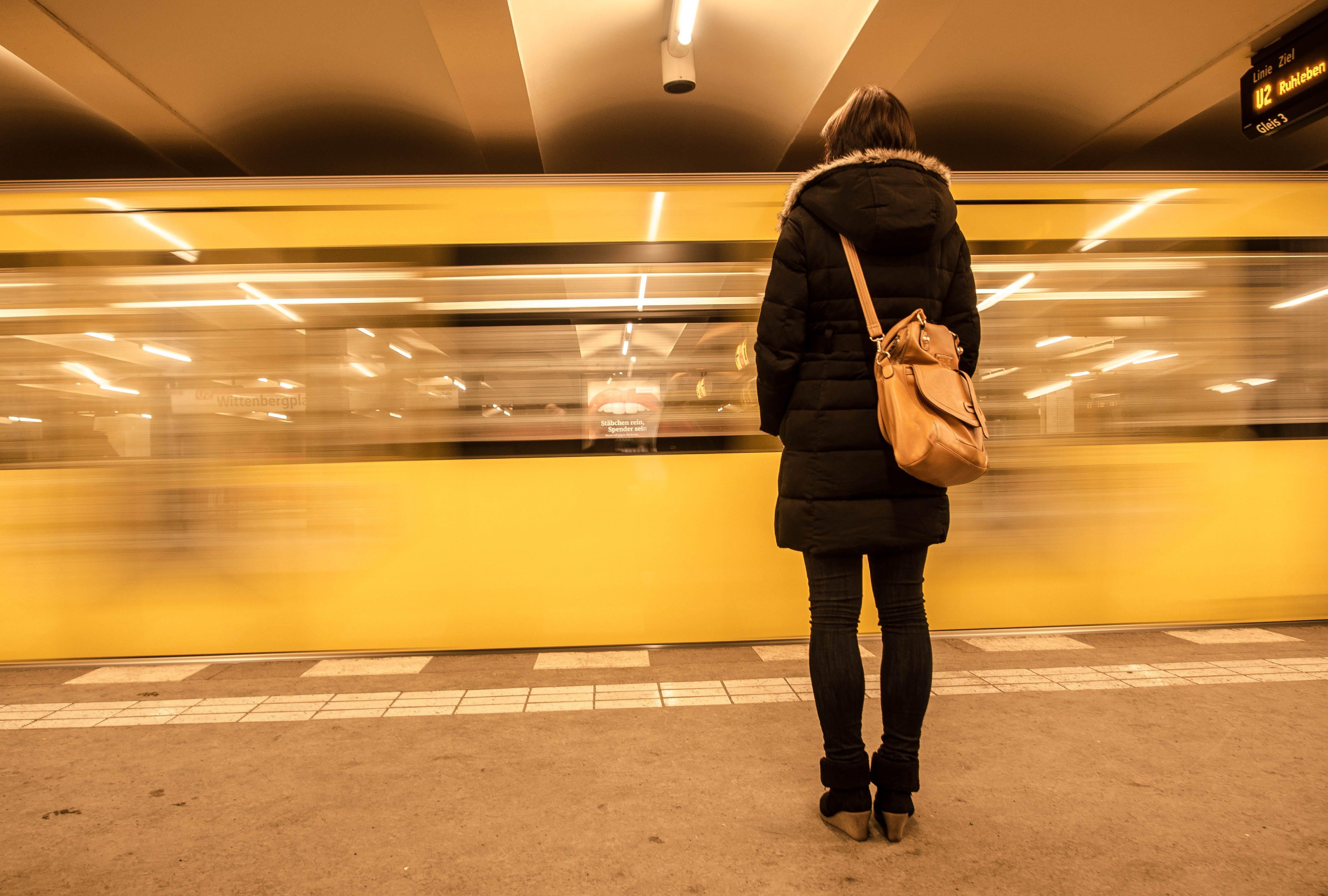 Mobilität und Gerechtigkeit: Eine Frau steht im Tunnelbahnhof vor der ausfahrenden Berliner U-Bahn.