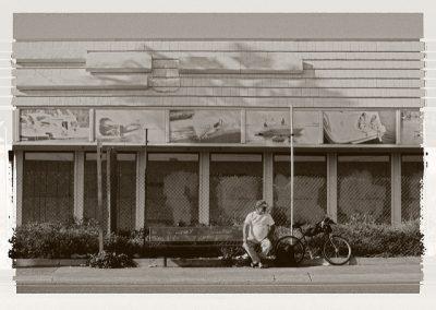 Ein Mann sitzt einsam auf einer Bank neben seinem Fahrrad