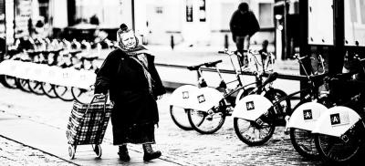 Eine ältere Frau mit Einkaufstrolley und Kopftuch geht an modernen Mieträdern vorbei