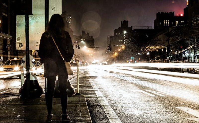 Eine Frau steht auf einer Verkehrsinsel inmitten einer vierspurigen Straße. Es ist dunkel und man sieht mehrere Autoscheinwerfer.