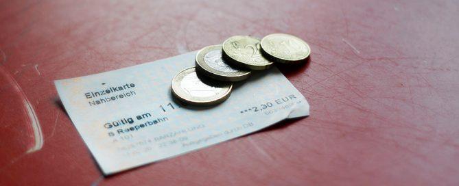 """Symbolbild einer HVV-Fahrkarte """"Nahbereich"""". Darauf liegen 2,30 Euro in bar. / Symbol photo of a HVV """"local journey"""" ticket. On top there's 2.30 Euro in cash."""